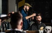 Hipster bearded client getting hairstyle. Barber with hairdryer works on hairstyle for bearded man, barbershop background. Styling concept. Barber with hairdryer drying and styling hair of client. poster