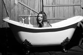 woman enjoys a hot bath. Beauty fashion model portrait. One beautiful sensual playful flirtatious young woman with long hair in blue knitted cloth sitting in white bath tub playing with soap foam indoor on wooden background, horizontal picture poster