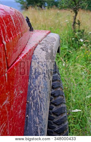 Dirty Mudguard Of Red Off Road Car  With Summer Nature Background
