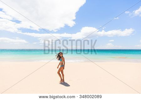 Beach vacation paradise Hawaii tourist woman walking on white sand wide perfect beach summer holiday in the Caribbean.