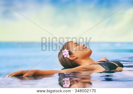 Luxury wellness spa resort Asian woman relaxing swimming in infinity pool at hotel. Caribbean tropical travel vacation getaway.