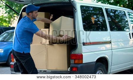 Male Courier Taking Delivery Boxes Out From Van, Moving Company, Goods Shipment