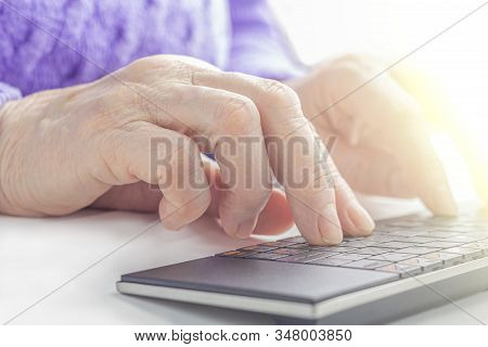 Elderly Woman's Hands Typing On A Pc Keyboard Close Up. Pensioner Working From Home. The Concept Of