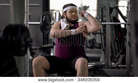 Man In Gym Pretending To Be Athletic, Looking At Biceps, Workout Motivation