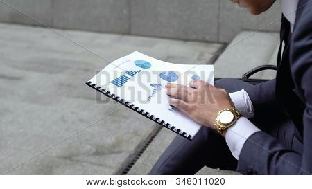 Economist Analyzing Graphs And Charts Before Important Meeting, Comparing Data