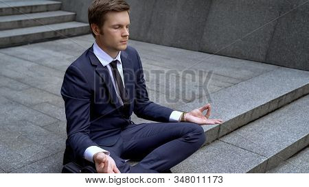 Young Businessman In Lotus Position Calming Down After Important Meeting, Stress
