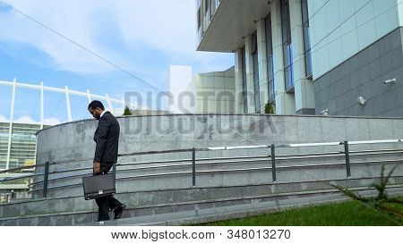 Overloaded Businessman Leaving Office At And Of Week, Depressed And Overloaded