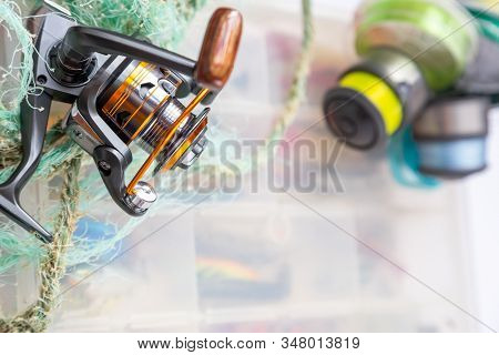 Different Fishing Tackles, Lines And Reel On Wooden Cork Background.