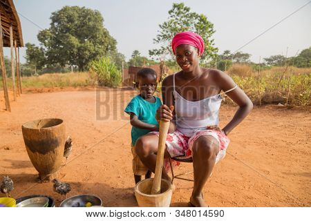 Bissau, Republic of Guinea-Bissau - January 5, 2020: Portrait of a young mother and her son, outside the city of Bissau, Guinea Bissau.