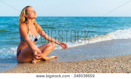 Woman In Yoga Pose Sitting By Sea