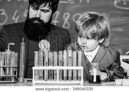 Teacher Man With Little Boy. Biology Science Lab. Father And Son At School. Learning Chemistry In Sc