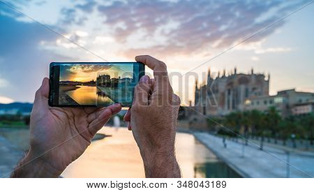 Men Using Her Smartphone For Take A Photo In Palma De Mallorca Islands At Sunset. In Background Cath