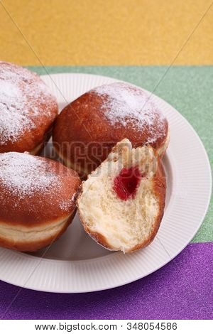 Sweet fat donuts for Mardi Gras purple, green, and yellow background