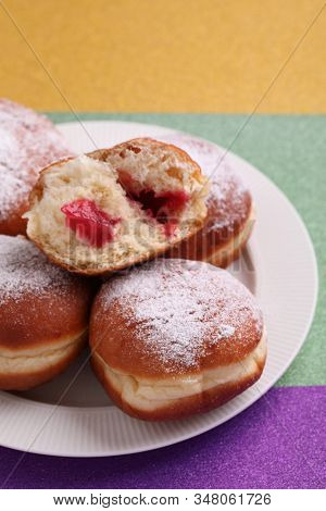 Sweet fat donuts on Mardi Gras purple, green, and yellow background. Traditional Mardi Gras food in America and Europe
