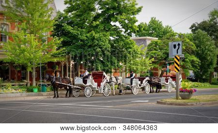 Niagara-on-the-lake, Canada - 06 19 2016: Horse Coaches Waiting For Tourists On The Queen Street Of