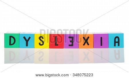 Bright Colorful Wooden Toy Blocks On A Reflective Surface Spelling Dyslexia. Learning Challenges Dis