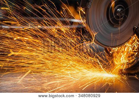 Close-up On The Sides Fly Bright Sparks From The Angle Grinder Machine. A Young Male Welder In A Whi