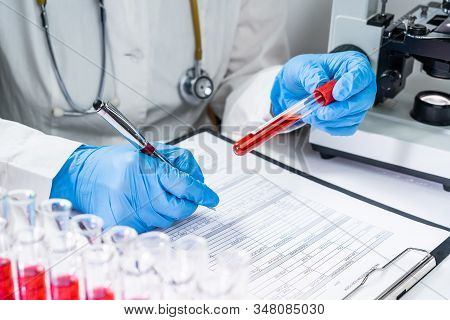 Blood Test Tubes. Senior Female Scientist Examining Blood Test Tubes At Her Laboratory Dna Testing