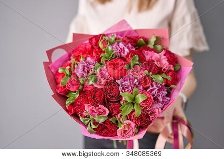 European Floral Shop. Beautiful Bouquet Of Mixed Flowers In Womans Hands. The Work Of The Florist At
