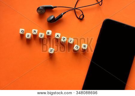 Black Modern Smartphone And Earphones On Trendy Orange Background. Dice With Letters Generation Z. Y