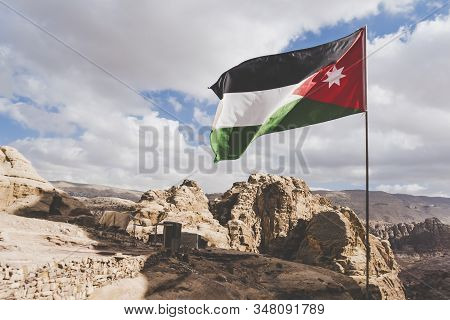 The Flag Of Jordan Blowing In The Wind In Petra, Jordan. Three-color Flag Of Jordan On The Backgroun