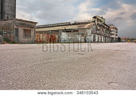 Wide Street In The Suburbs Of The City With Abandoned Warehouse And Factory - Desolate Landscape In