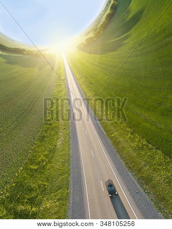 Car Driving On The Highway From The Sun At Sunset Surrounded By Fields With Green Grass