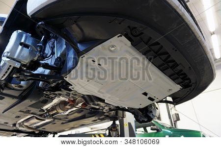 White Luxury Car Raised On A Lift In Service. An Additional Crankcase Protection Is Installed On The