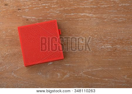 Red Wireless Speaker On Wooden Background, Top View