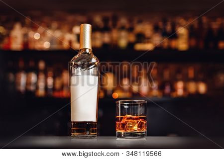 Glass Of Whiskey Bottle With Ice Stands On Bar Counter, Dark Brown Background