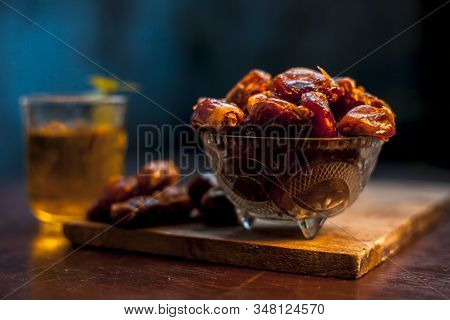 Close Up Of Raw Dates Along With Its Syrup In A Glass With Some Mint Leaves On It Which Helps In Wei