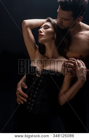Handsome Muscular Man Hugging Sensual Woman In Corset Isolated On Black