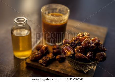 Dates Syrup In A Glass Along With Some Raw Dried Dates And Some Cooking Oil In A Glass Bottle On A W
