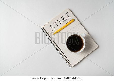 Notice Start In Notebook. Words Handwritten. Notepad And Cup Of Coffee On White Background