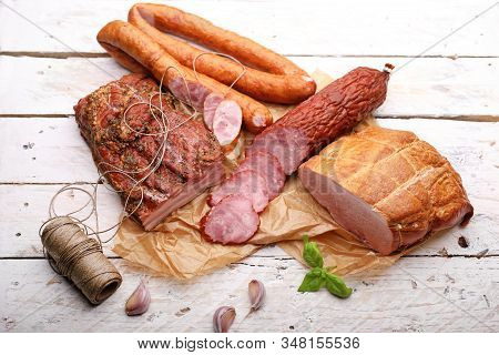 Traditional Smoked Cold Cuts On A Paper And Wooden Boards. Classic Meat Products.