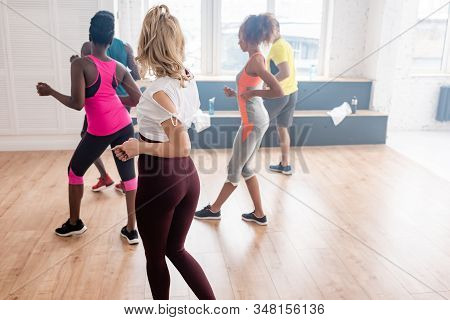 Selective Focus Of Multicultural Zumba Dancers Practicing Movements In Dance Studio