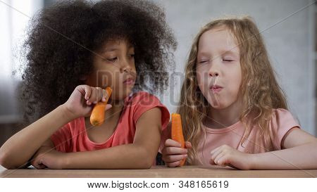 Cute Little Girl Looking At Friend Eating Carrots With Appetite, Healthy Food