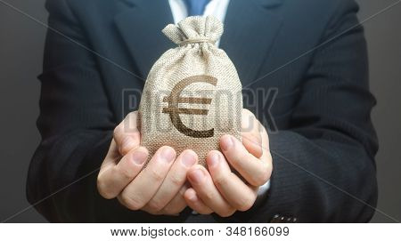 A Man Holds Out A Euro Money Bag. Granting Financing Business Project Or Education. Provision Cash F