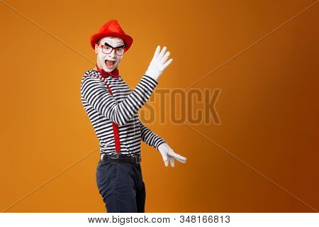 Mime male in white gloves and red hat looking at camera on orange background