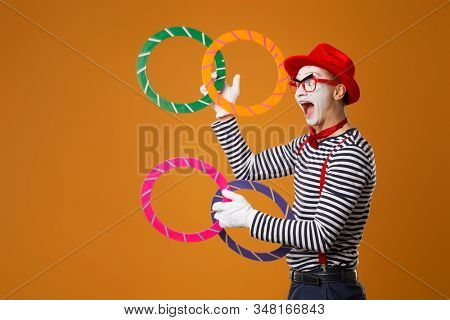 Happy mime with multi-colored rings on orange background