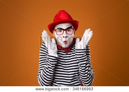 Surprised mime in red hat and vest on orange background