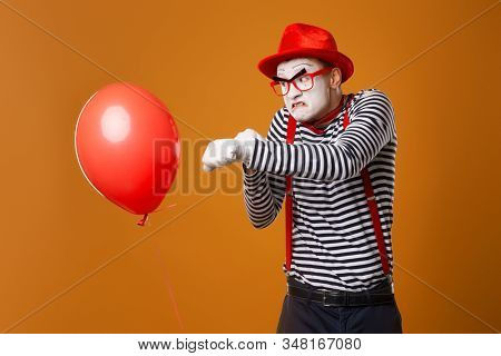 Evil clown mime box with red ball on orange background