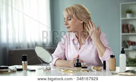 Middle-aged Woman Looking In Mirror At Face After Skin Rejuvenation Procedure