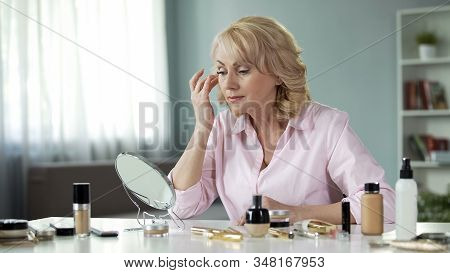 Blond Female In Her 50s Looking Attentively In Mirror, Anti-wrinkle Cosmetics