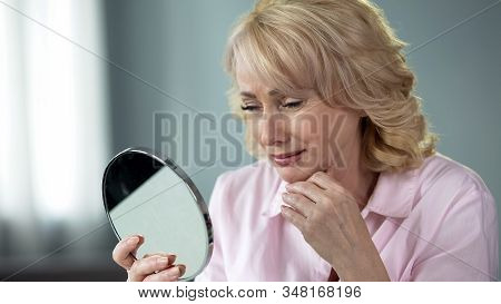 Lady In Her 50 Looking In Mirror Remembering Young And Healthy Skin, Nostalgia