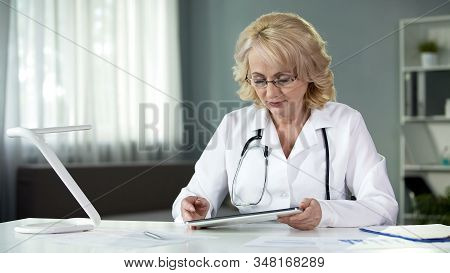 Female General Practitioner Reading Patient's Online Medical Records On Tablet