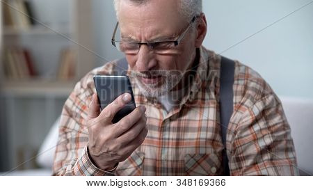 Old Man Looks Incredulously At Cellphone, New Technology Complicated For Elderly