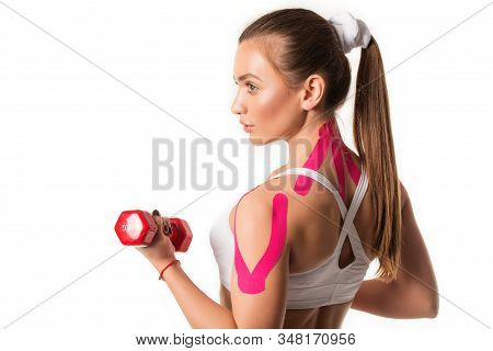 Cute Young Girl Athlete Fitness Trainer Holding Red Dumbbell In Hands With Pink Stickers On Her Shou
