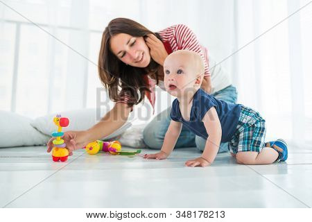 Charming Cute Cheerful Boy With A Happy Caring Mom At Home In A Bright Living Room. Concept Of Child