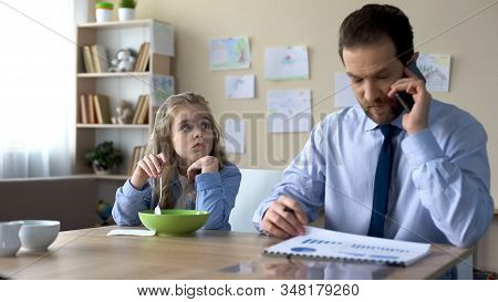 Sad Daughter Looking At Busy Father Ignoring Her, Lack Of Parental Attention